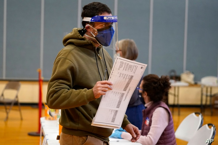 Julian St. Laurent wear a face shield and two face masks to help prevent the spread of the coronavirus as he walks to a voting…