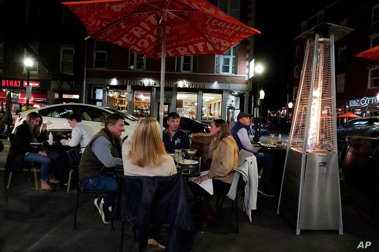 Diners have dinner outdoors, Friday, Nov. 6, 2020, in Boston's North End. More stringent coronavirus restrictions are now in…