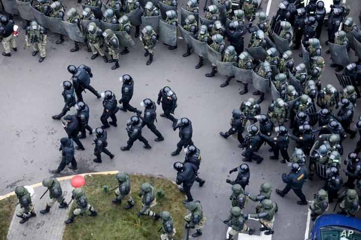 Belarusian riot police block the road to stop demonstrators during an opposition rally to protest the official presidential election results in Minsk, Belarus, Nov. 15, 2020.
