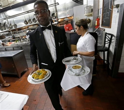 Waiter Austin Murray brings plated dishes from the kitchen to the dining room at Antoine's Restaurant in New Orleans, Sept. 11, 2015.