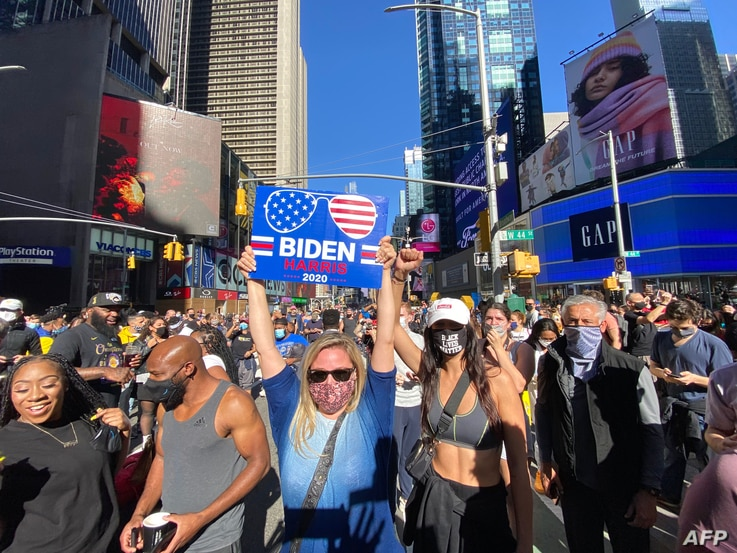 People celebrate at Times Square in New York City after Joe Biden was projectd the winner of the 2020 presidential election, Nov. 7, 2020.