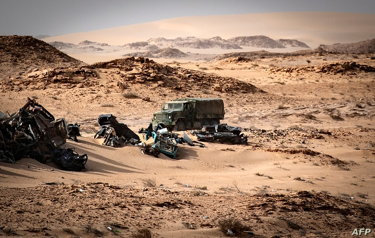 A Moroccan army vehicle drives past car wreckages in Guerguerat located in the Western Sahara, after the intervention of the royal Moroccan armed forces in the area, Nov. 24, 2020.