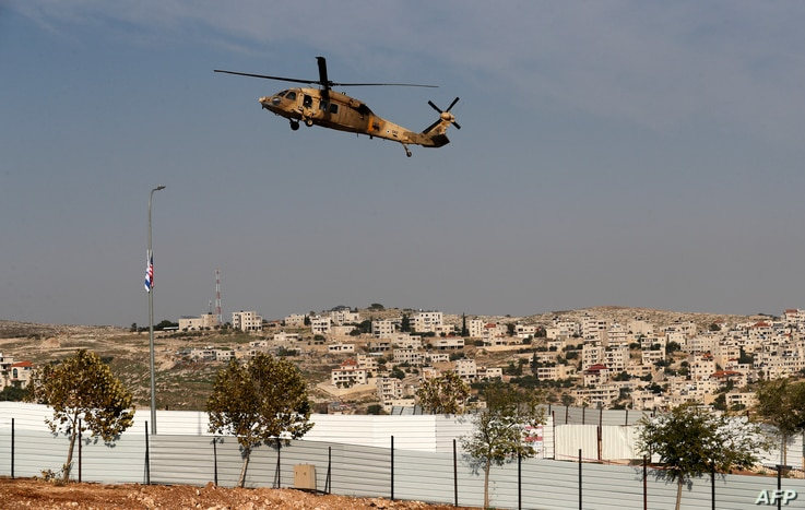 An Israeli Air Force Blackhawk helicopter carrying U.S. Secretary of State Mike Pompeo hovers over an industrial park near the Israeli Psagot settlement in the occupied West Bank, north of Jerusalem, Nov. 19, 2020.