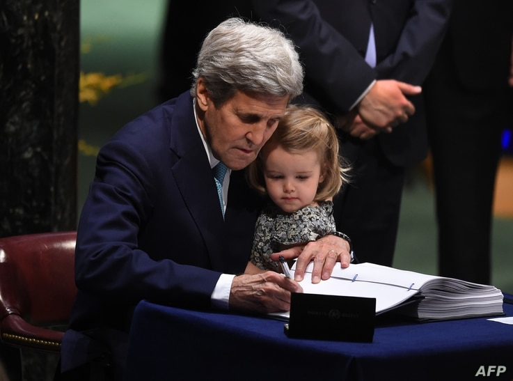 FILE - Then-U.S. Secretary of State John Kerry holding his granddaughter, Isabelle Dobbs-Higginson, signs the book during the signature ceremony for the Paris Agreement at the United Nations General Assembly Hall, April 22, 2016, in New York.