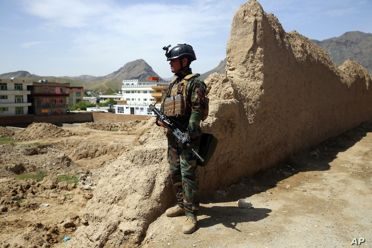 FILE - An Afghan commando stands guard at the site of a suicide bomb attack on the outskirts of Kabul, April 29, 2020.