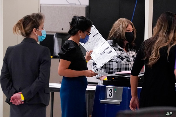 The Maricopa County Elections Department officials conduct a post-election logic and accuracy test for the general election as observers watch the test, Nov. 18, 2020, in Phoenix, Arizona.