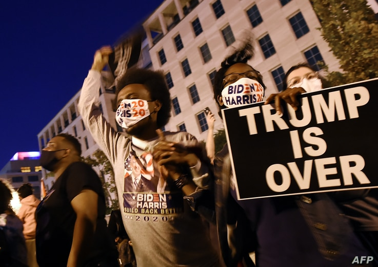 FILE - African American supporters of president-elect Joe Biden celebrate on Black Lives Matter Plaza across from the White House in Washington, Nov. 7, 2020, after Biden was projected the winner of the 2020 presidential election.