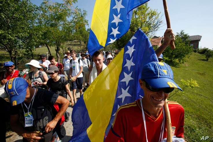 """FILE - Participants of the """"March for Peace,"""" carrying Bosnian flags, walk near the village of Nezuk, some 150 kilometers northeast of Sarajevo, July 8, 2015."""