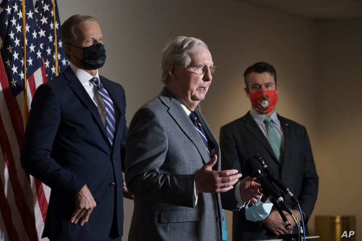 Senate Majority Leader Mitch McConnell, R-Ky., flanked by Sen. John Thune, R-S.D., left, and Sen. Todd Young, R-Ind., talks to reporters on Capitol Hill in Washington, Nov. 17, 2020.