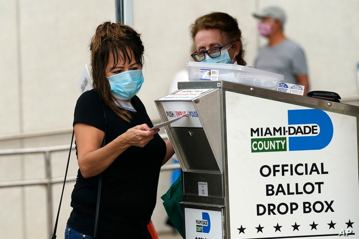 FILE - An election worker places a vote-by-mail ballot into an official ballot drop box outside of an early voting site in Miami, Florida, Oct. 19, 2020.
