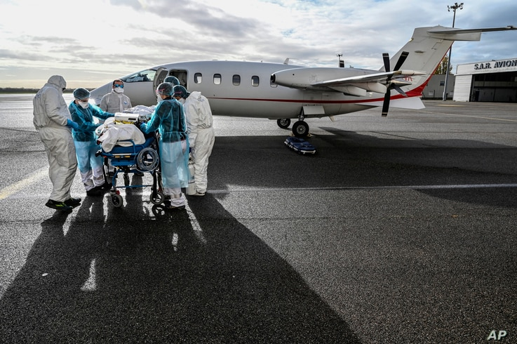 Medical staff transport a patient affected with COVID-19 to be evacuated to another hospital, at Bron airport near Lyon, central France, Nov. 16, 2020.