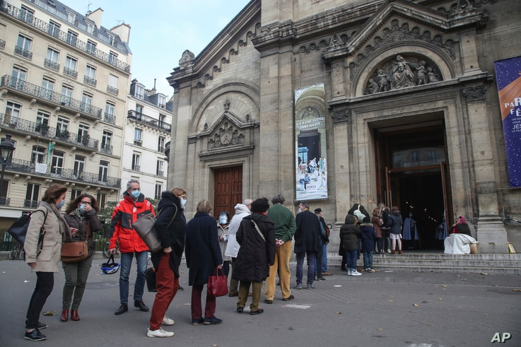 Church-goers wearing face masks lineup outside the Notre-Dame-des-Champs church in Paris, France.