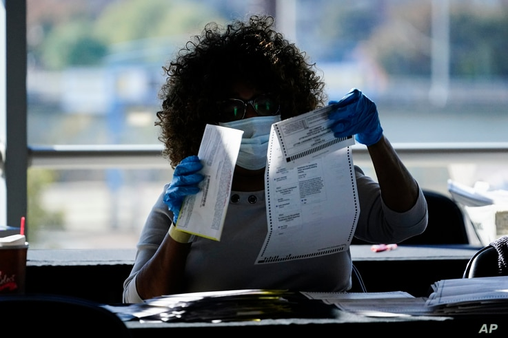 An election personnel examines a ballot as vote counting in the general election continues at State Farm Arena in Atlanta, Georgia.
