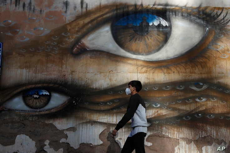 A boy wearing a face mask to help curb the spread of the coronavirus walks past a mural by British street artist My Dog Sighs, in Rome's Trastevere neighborhood, Italy, Nov. 9, 2020.