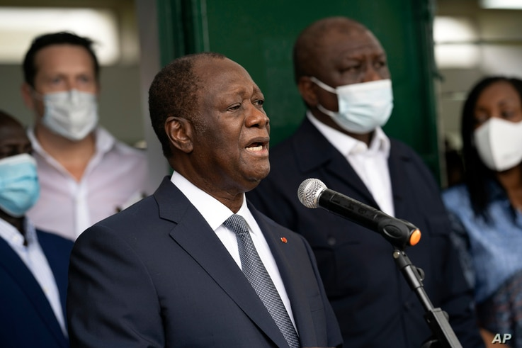 Ivory Coast President Alassane Ouattara speaks to journalists after voting at a polling station during presidential elections in Abidjan, Oct. 31, 2020.