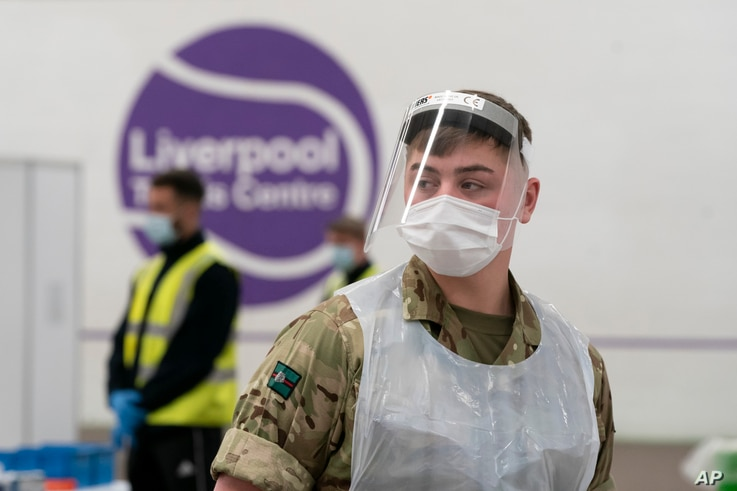 A member of the armed forces waits to test local residents at the Liverpool Tennis Centre on the first day of mass testing pilot, in Liverpool, Britain, Nov. 6, 2020.