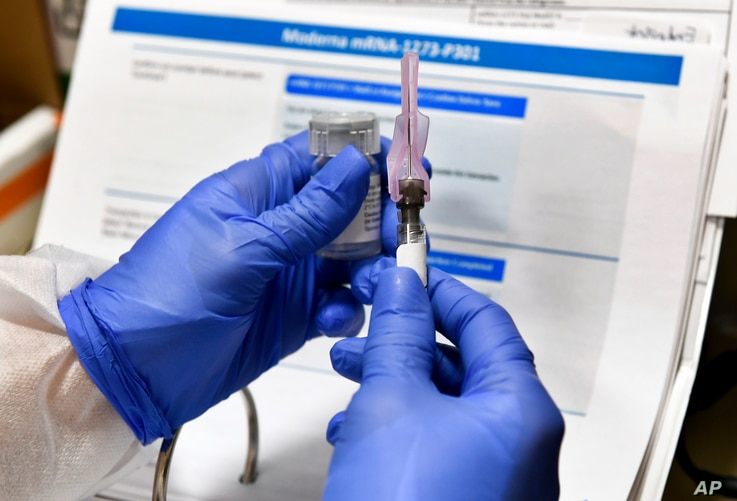 FILE - A nurse prepares a shot that is part of COVID-19 vaccine developed by the National Institutes of Health and Moderna Inc., in Binghamton, New York, July 27, 2020.