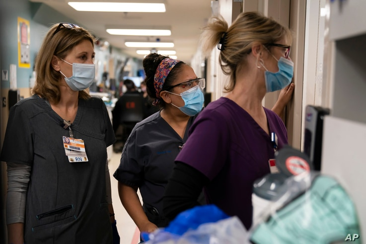 FILE - Nurses watch as medical workers try to resuscitate a COVID-19 patient in the emergency room at Providence Holy Cross Medical Center, in the Mission Hills section of Los Angeles, California, Nov. 19, 2020.