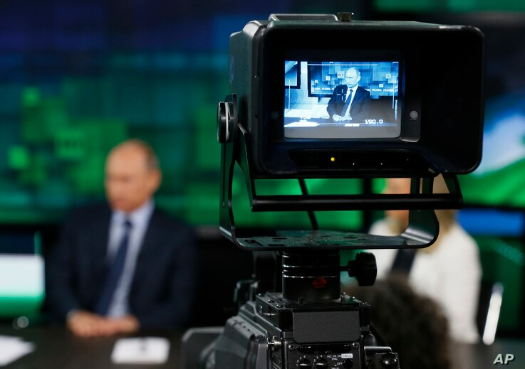 FILE - Russian President Vladimir Putin is seen in the screen of a camera viewfinder in a studio of Russia's RT television channel in Moscow, Russia, June 11, 2013.