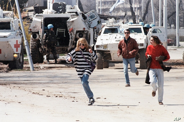 """FILE - Civilians run along Sarajevo's notorious """"Sniper Alley,"""" as French U.N. peacekeepers look on, April 5, 1995."""