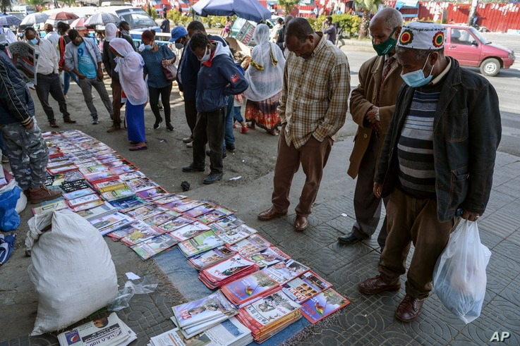 Ethiopians check newspapers and magazines reporting on the current military confrontation in Ethiopia's Tigray region, at a news stand on a street in the capital Addis Ababa, Nov. 7, 2020.
