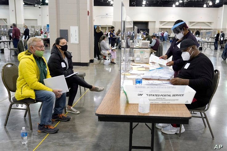 Election workers, right, verify ballots as recount observers, left, watch during a Milwaukee hand recount of presidential votes at the Wisconsin Center, in Milwaukee, Wisconsin, Nov. 20, 2020.