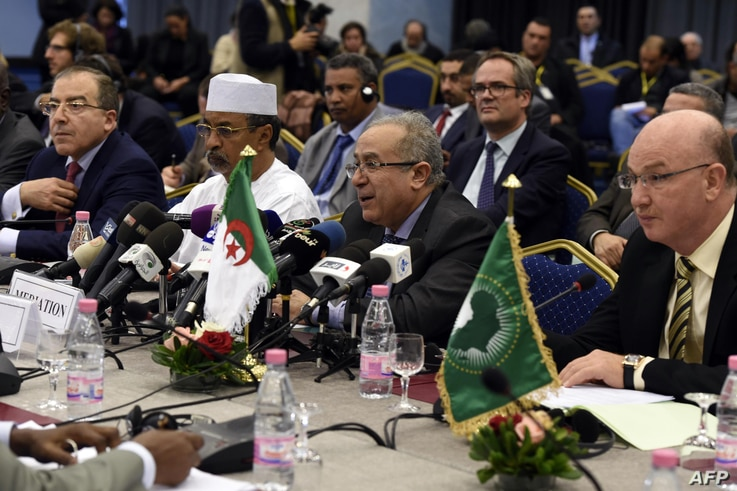 Algerian Foreign Minister Ramtane Lamamra (C) speaking during a meeting for a peace agreement between the Malian government and…