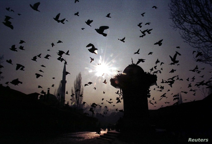 FILE - A flock of pigeons fly over Bascarsija square in the old part of Bosnia and Herzegovina's capital Sarajevo, Jan 11, 1998.