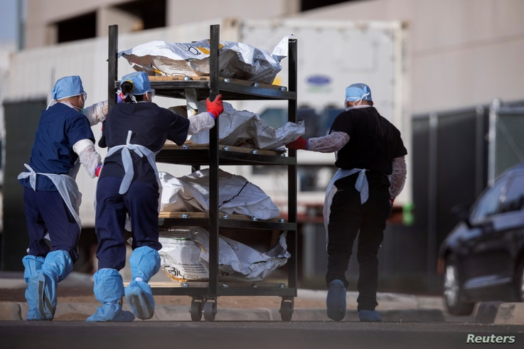 """El Paso County Medical Examiner's Office staff roll bodies that are in bags labeled """"Covid"""" from refrigerated trailers into the morgue office amid the COVID-19 outbreak, in El Paso, Texas, Nov. 23, 2020."""