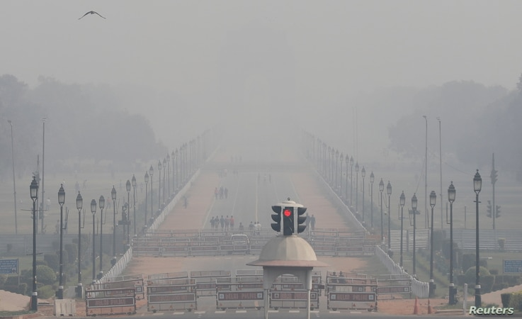 People walk near India Gate on a smoggy afternoon in New Delhi, India, Nov. 15, 2020.