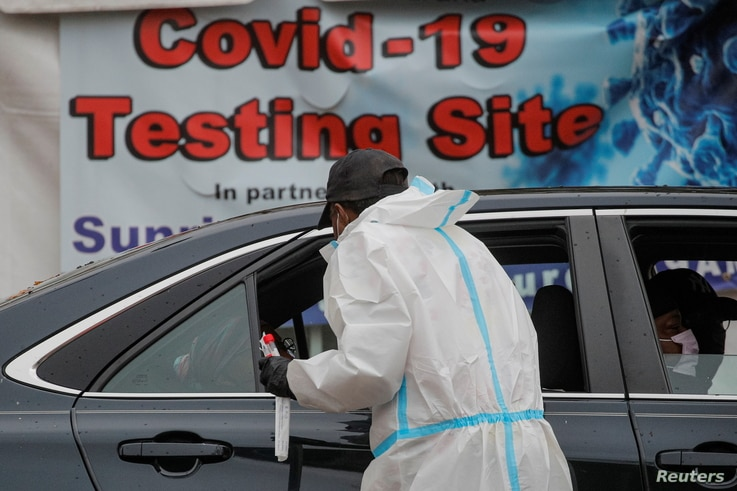 A healthcare worker takes a swab from a person sitting in a car at a drive-thru COVID-19 test center in Newark, New Jersey, Nov. 12, 2020.