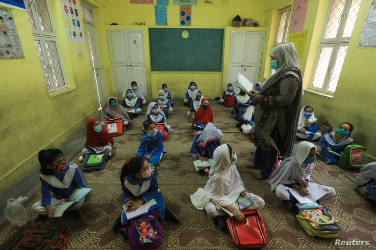 FILE - Students wear protective face masks, maintaining a safe distance as they attend a class after the provincial government allowed reopening both primary and lower secondary classes amid the COVID-19 pandemic in Peshawar, Pakistan, Sept. 30, 2020.