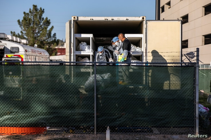 El Paso County detention inmates, Sheriff officers and morgue staff help move bodies to refrigerated trailers deployed during a surge of COVID-19 deaths, outside the Medical Examiner's Office in El Paso, Texas, Nov. 14, 2020.