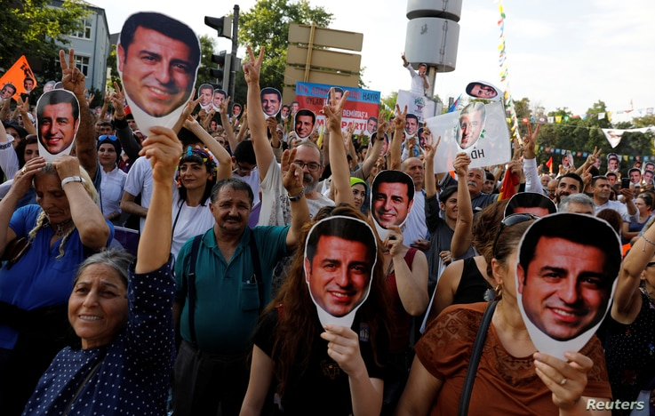 Supporters of Turkey's main pro-Kurdish Peoples' Democratic Party (HDP) hold masks of their jailed former leader and presidential candidate Selahattin Demirtas during a rally in Ankara, June 19, 2018.