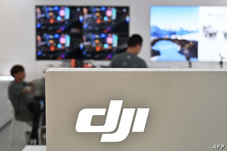 People are seen in a DJI store in Shanghai on May 22, 2019. (Photo by Hector RETAMAL / AFP)