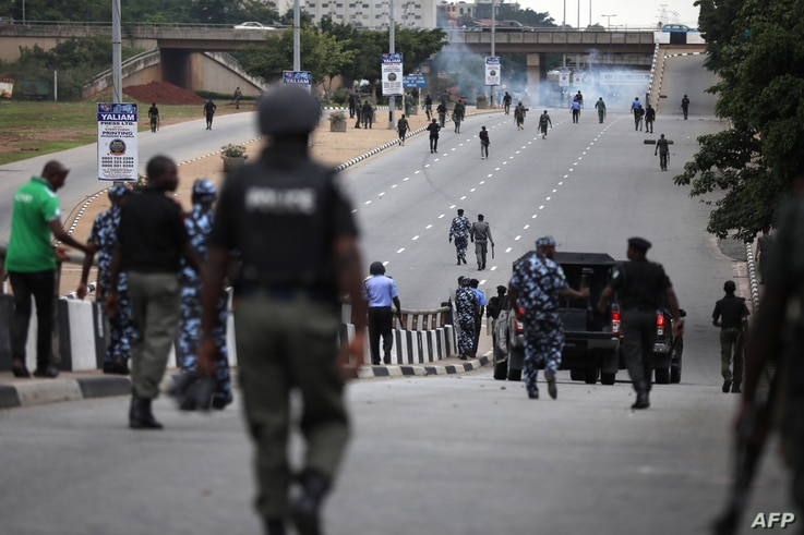 Nigerian police officers patrol in the streets of Abuja during clashes with members of the shiite Islamic Movement of Nigeria …