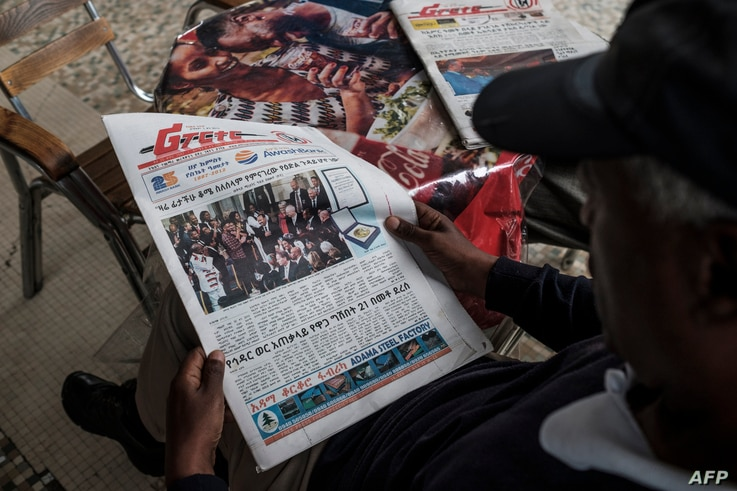 A man reads the Ethiopian Reporter newspaper with the cover showing  the Peace Nobel Prize ceremony for Ethiopia's Prime…