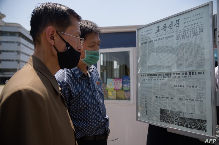 People read an article condemning anti-Pyongyang leaflets sent across the border by South Korean activists, at a news stand in…