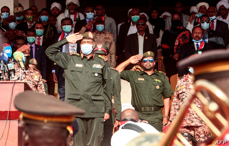 Chairman of Sudan's Sovereignty Council General Abdel Fattah al-Burhan (C-L) performs a military salute during a reception…