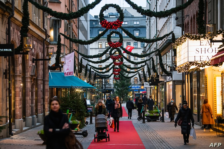 People walk past shops under Christmas decorations in Stockholm on December 3, 2020, during the novel coronavirus COVID-19…