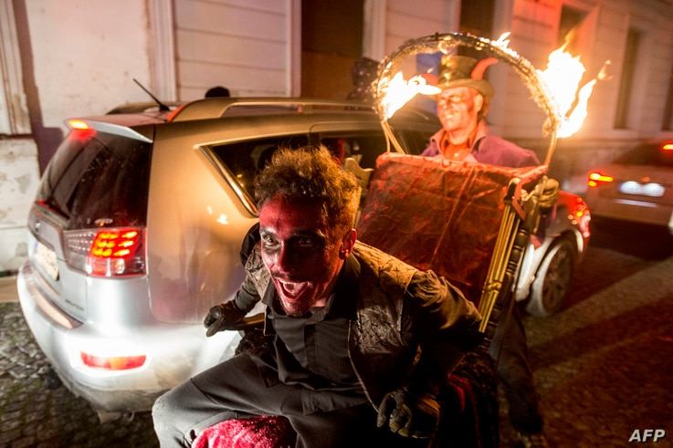 Members of the new circus company Cirk La Putyka dressed as Devils entertain people during their drive-thru performance on…