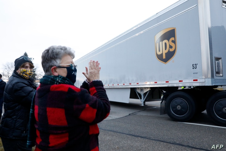 Nancy Galloway (L) and Susan Deur cheer as trucks carrying the first shipment of the Covid-19 vaccine that is being escorted by…