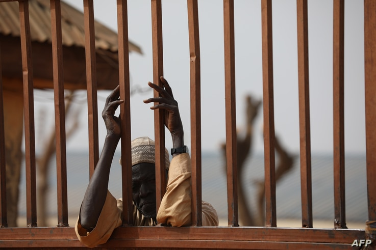 A parent waits outside the Government Science Secondary school in Kankara, in northwestern Katsina State, Nigeria on December…