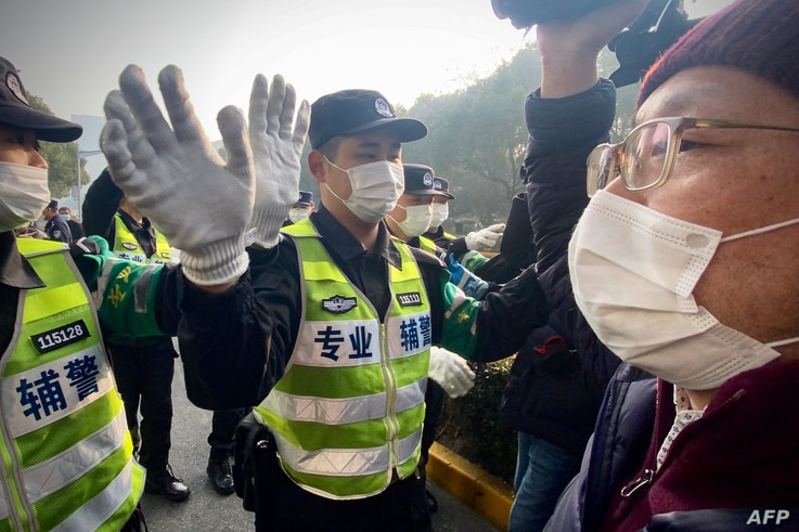 Police attempt to stop journalists from recording footage outside the Shanghai Pudong New District People's Court, where…
