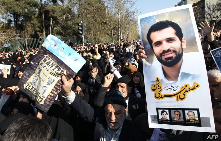 Iranians hold a portrait of assassinated nuclear scientist Mostafa Ahmadi-Roshan (R) and a wanted poster with portraits of US…