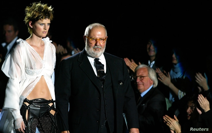 Italian designer Gianfranco Ferre(R) acknowledges the applause on thecatwalk with top model Stella Tennant (L) after…