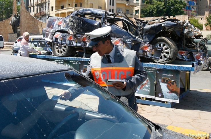 A policeman passes out leaflets with road accident statistics, in front of a destroyed car which is put on display, during a…