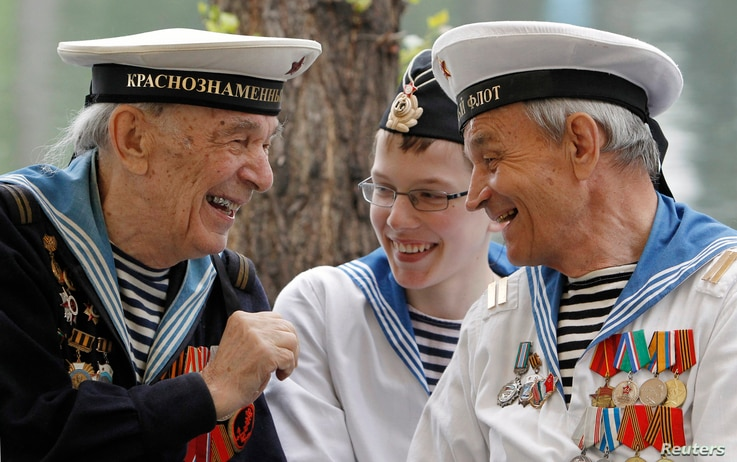 World War II veterans share a joke, as a boy wearing a navy uniform listens to them, during a Victory Day celebration in Gorky…