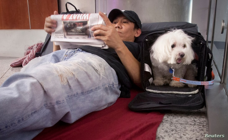 Stranded passenger Danny Nguyen and his dog Lucky wait as they spend the night on the floor of LaGuardia airport after his…