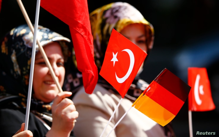A Turkish woman waves a Turkish and a German flag during a demonstration including members of the Turkish ultra-nationalist…